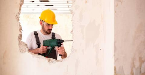 klusjesman, verbouwing, gaten in de muur, klussen, man, verzekeringen, schade zakelijk, gele beschermingshelm